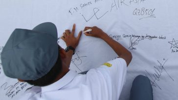 Seorang siswa membubuhkan tanda tangan untuk korban kecelakaan AirAsia QZ 8501 di SMA Negeri 2 Medan, Sumut, Senin (5/1). Ratusan siswa menggelar doa bersama dan aksi seribu tanda tangan sebagai bentuk kepedulian dan belasungkawa atas jatuhnya pesawat AirAsia. ANTARA FOTO/Septianda Perdana/Rei/ama/15.
