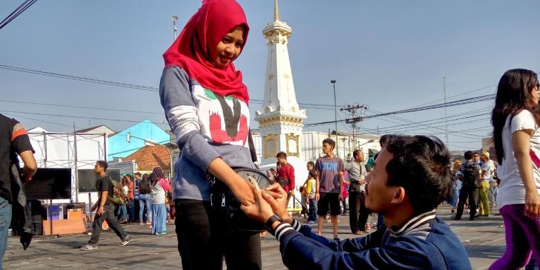 Nanang Kristanto (28), ketika melamar kekasihnya Dian Paramita (24), ketika momen gerhana matahari di Tugu Yogyakarta berlangsung, Rabu (9/9/2016) di pagi hari. (Kompas.com)